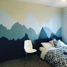 Freehand mountains painted on bedroom wall.