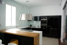 SANTOS kitchen | Black bright lacquered Minos model in Valencia, project by Entrecuines Estem