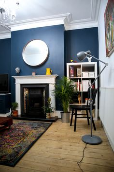 Victorian Mid Terrace Living Room. Farrow and Ball Hague Blue on the wall, original fireplace, pallet coffee table, Kallax bookshelf and Stockholm mirror from Ikea.