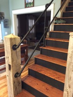 Reclaimed barn timber used as newel post w galvanized pipe handrail painted black.