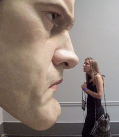 """A woman looks at """"Mask"""" by Ron Mueck during a preview of an exhibit of young British artists called """"Sensation"""" at the Brooklyn"""