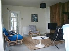 Open plan living and dining with wood burner in Cornish beach house to let at www.ourbeachbreak.com
