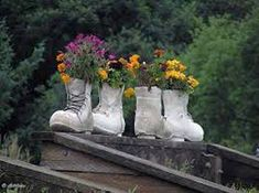 Painting old boots white for making bright handmade planters.