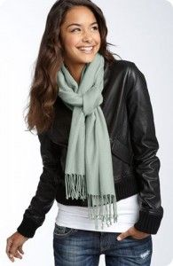 Fold the scarf in half and put it around the back of your neck with a loop on one side. Pull one of the scarf ends through the loop. Twist the loop. Pull the other scarf end through the loop.