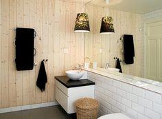 For å bryte opp på badet har eierne valgt å ha en vegg med panel. Lampen med skog er fra Ikea, flisene er fra Megaflis, mens vasken er fra Kvik.