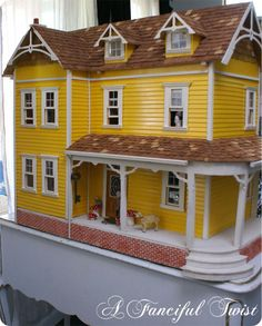 Yellow_dollhouse of Vanessa  from the blog ' A Fanciful Twist' I built one like this from a kit, it's slate blue/gray instead of yellow