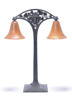 Edgar Brandt  A Wrought Iron Table Lamp, circa 1925  with open scroll work foliate detail to the top of the stem, supporting two internally mottled orange glass shades, probably later  49cm high, stamped 'E.Brandt'