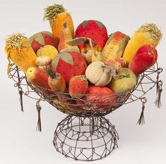 """A thirty-three-piece collection of velvet fruits and vegetables in brilliant colors, rare forms, and beautiful condition. Included in the grouping is a rare ear of corn, three very large carrots, strawberries, melons, a tomato, a mushroom, and some rare miniatures. Height 16"""", width 18""""."""