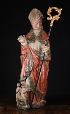 Polychrome Wood Carving of Saint Nicholas with hollowed back - The bearded saint depicted wearing a Mitre and cloak draped over long white habit, holding a Crozier in one hand, and with three children emerging from a barrel at his feet (Referencing the miracle of bringing 3 murdered children back to life) - 40 inches tall (102 cm) - Flemish - 16th century