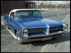 1964 Pontiac Bonneville Convertible. It was dark blue with lt/dk blue leather interior and a white top. My first convertible..