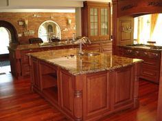 yellow-and-brown-granite-countertops-brown-classic-wooden-kitchen-cabinets-brown-classic-wooden-flooring