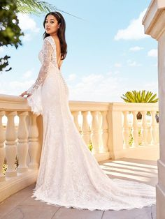 Val Stefani style Piper is a lace low back wedding dress with buttons and sheer long bell sleeves. #lowback #classic #longsleeveweddingdress #laceweddingdress #lacewedding #weddinginspo #fairytale