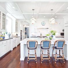 White kitchen, clean traditional, island, white cabinets, farmhouse sink, tounge and groove ceiling detail, rattan chairs,