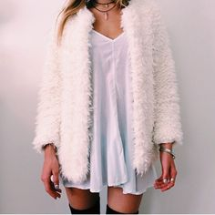 fuzzy white coat and white slip dress and tall black boots
