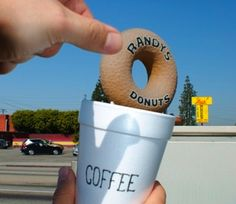 scale-the donut in this picture is actually a huge donut on top of a building and its way bigger than his cup or hand