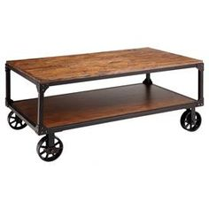"""Industrial-inspired coffee table with cast metal wheels and an open bottom shelf.    Product: Coffee tableConstruction Material: Wood veneers and cast metalColor: Antique brown Features: One storage shelfDimensions: 19"""" H x 46"""" W x 26"""" D"""
