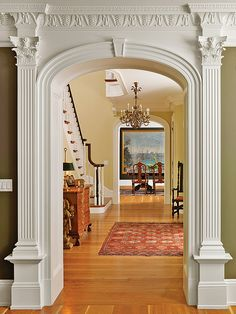 glossy wood floors and beautiful mouldings in this hallway to the stairs.