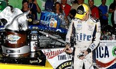 Brad Keselowski breaks off a champagne bottle in his hands during the celebration in victory lane at Kentucky Speedway.