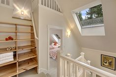 A clever ships ladder bookcase/stair leads to a third level loft tucked under the eaves. Bookcase Stairs, Rustic Bookcase, Loft Stairs, Bookcases, Cute Cottage, Cottage Image, Ship Ladder, House Plans, Cottages
