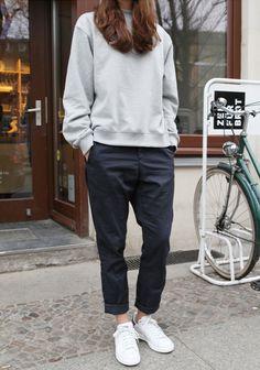 Grey sweatshirt, white sneakers, black pants.