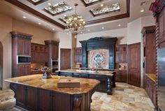 A cavernous luxury kitchen with ornately carved cabinetry, skylights, and a chandelier between the two islands