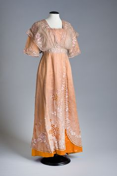 Evening Dress: Orange silk satin with an overdress of mushroom coloured chiffon (pink shot with green). A loose fitting bodice with squared neckline and raglan sleeves, with a slim straight ankle-length skirt. The over bodice has a shawl collar, the overdress is trimmed with pink silk embroidery. Fastened with metal hooks, thread loops, and press- studs, and a silk drawstring. The bodice and sleeves are lined with cream cotton damask, with dress protectors, the hem is lined with cream wool.