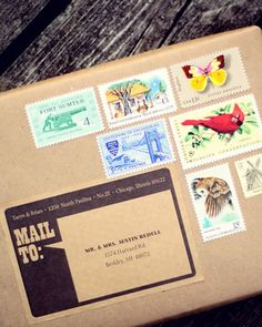 The invitation is packaged in a small paper box, wrapped in kraft paper and covered in a mixture of vintage stamps.