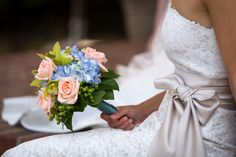 Blue hydrangeas with hypericum green berries, green orchids, and peach roses