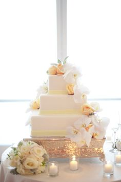 White cake with pastel yellow flowers and details. So lovely.