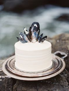 ocean-themed wedding cake on vintage trays—love how their time-worn patina picks up the surrounding colors of the rocks and ocean surf