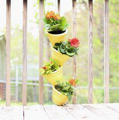 jardin vertical sur le balcon avec tour de pots de fleurs empilés et faussement inclinés