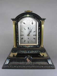 """Edward Funnell, Brighton. A Victorian ebonised bracket clock in the 17th Century style, ormolu mounted, having an arched  topped silvered Roman dial set chime and rise and fall dials, set  quarter repeating triple fusee movement, striking 8 bells and  chiming gong, the case of architectural form, painted with  flowers and insects, mounted Corinthian columns on scroll feet  and plinth bracket base 16""""h x 15.5""""w x 9.5"""""""
