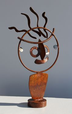 Rusted steel and stainless steel figurative sculpture about two feet tall