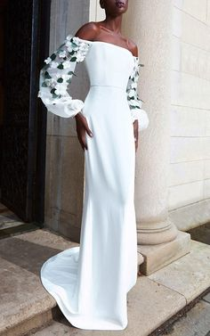 Elizabeth Kennedy ~ ~ ~ Off-The-Shoulder White Gown With Sheer White Organza Embellished Full-Length Puffy  Sleeves with Green Leaves and White Gardenia type flowers with pearl & crystal centers.  The dress itself is fully lined. The short rear train is obvious in this picture, thereby a full scale TRIP ALERT.       Moda Operandi.com    .