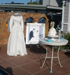 I love, love, love the idea of displaying your wedding photo, cake topper and DRESS on your 50th wedding anniversary. So sweet and romantic. : )