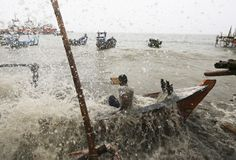 A fisherman falls in his wooden boat as it is hit by strong sea waves, and breaks, in water off the north coast of Jakarta March 10, 2014. REUTERS/Beawiharta