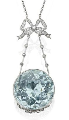 An Edwardian aquamarine and diamond pendant The pendant formed of a scrolling ribbon bow set with single-cut diamonds suspending two diverging knife-edge bars each with three single-cut diamond highlights, supporting a collet-set circular-cut aquamarine, all to a delicate trace-link neckchain, pendant length 47mm, chain length 40cm, the aquamarine estimated to weigh approximately 28cts, to a fitted case retailed by Wilson & Sharpe, Edinburgh