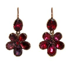 "Georgian Garnet Pansy Earrings. The name Pansy is derived from the French word pensée meaning ""thought"". The flower  became synonymous with the phrase ""thinking of you"", often as a gesture of sentiment. Here flat cut almandine garnets are set closed back in 9k yellow gold form a five petal pansy flower earring a symbolic token of love.  English in origin, found in London. Later ear wires. Circa 1800-30."