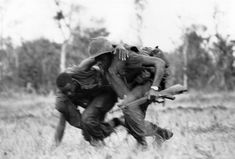 """A marine helps his wounded comrade to cover despite North Vietnamese fire during battle on May 15, 1967 in the western sector of """"Leatherneck Square"""" south of the demilitarized zone in South Vietnam. (AP Photo/John Schneider)"""