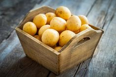 #Potatoes in wooden box  Potatoes in wooden box on table.