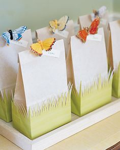 Green gift bag and an off-white lunch bag that has the same-size base Scissors Double-sided tape Hot-glue gun Miniature clothespin Fabric butterfly Name tags