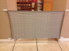 Fabric Baby Gate for Iz. Maybe two hooks at the top and a shower rod at the bottom (that touches the floor) so you don't have to bend over and unhook the bottom one.