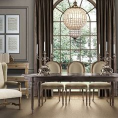 The grand chandelier in this dining room is perfect for the height of this room and is in perfect proportion with the large window behind it, making an elegant statement when you walk into this area.