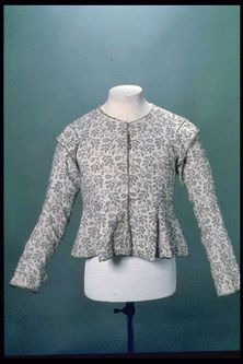 Woman's close-fitting long sleeved jacket, with centre-front fastening and a round neck, embroidered with fine black wool in a pattern of barberries. Production Date: 1610-1620 ID no: 59.77a Museum of London