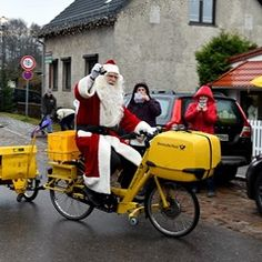 Father Christmas arrives into Himmelpfort town on his yellow bicycle