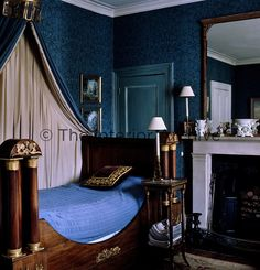 The spare bedroom has a mahogany lit bateau and blue patterned wallpaper