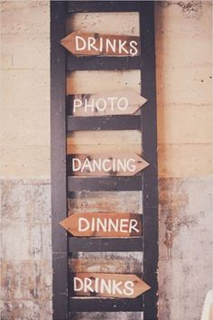 Rustic wedding welcome sign hung on ladder shows direction of events.