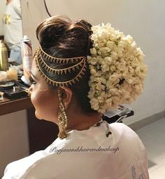 What a beautiful large low bun with real flower adornment! Care however should be taken before adopting such hairstyles, as due to it's high static charge, it will cause phlegm to move up in the throat, causing the voice to quaver & a frequent urge to clear the throat. A heavy chabi chhalla with a long & wide hook if inserted at the edge of the pleats of the saree, will reduce this problem as it's hook will activate the acupressure points that act to keep the throat clear.