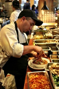 Xoco Restaurant Chef Alonso topping Xoco's red chile - lamb caldo with crispy potatoes!