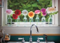 Simple bottles with bright blooms on the window ledge in the sunroom #styledby